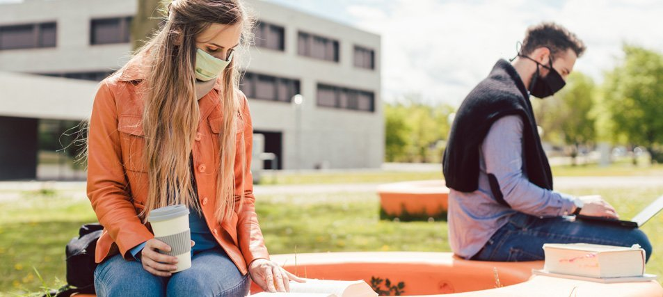 two students in mask studying on campus