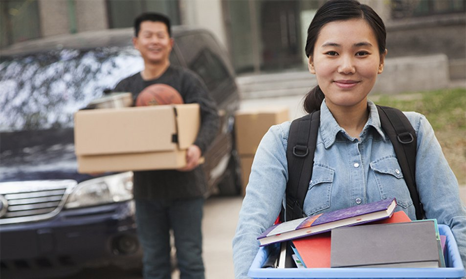 College student walking into college dorm carrying a box of books.